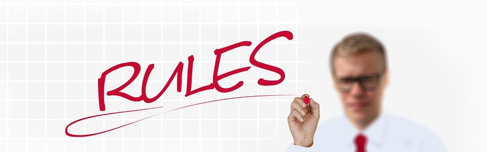 """Mann mit Brille schreibt Schriftzug """"Rules"""" (Regeln) auf ein whiteboard. Credit: Gerd Altmann, Pixabay"""