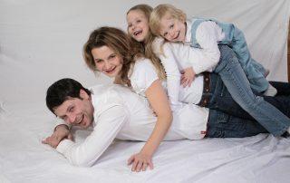 Symbolbild Familie: Mann, Frau, Mädchen, Junge liegen am Boden übereinander