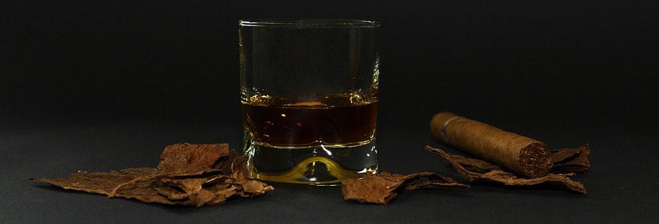 Symbolbild Alkohol und rauchen: Whiskeyglas und Zigarre auf dunklem Hintergrund, Foto: annca, Pixabay
