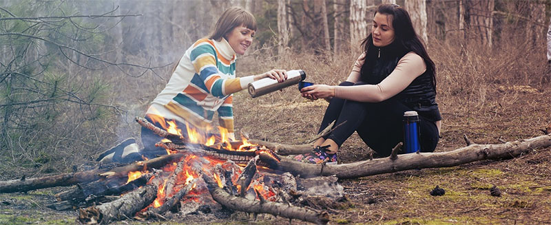 Symbolbild Freundschaft: zwei jungen Frauen am Lagerfeuer