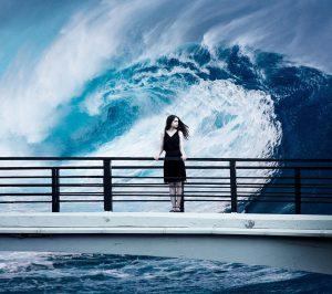 junge Frau steht auf einer Brücke am Meer, hinter ihr i9st eine riseige Welle zu sehen, Credit: Sarah Richter, Pixabay