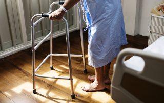 Symbolbild Pflege: Frau steht mithilfe eines Rollators neben einem Pflegebett, Credit: rawpixel, Pixabay