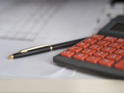 Taschenrechner und Kuli liegen auf einem weißen Blatt Papier, Credit: edar, Pixabay