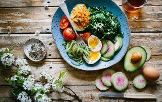 Symbolbild gesunde Ernährung: Teller auf Holztisch mit Gemüse, Ei, Samen und Rohkost, Photo by Brooke Lark on Unsplash