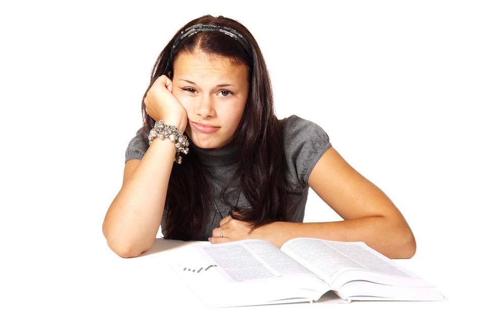 Schülerinnen sitzt vor einem Buch und sieht traurig aus, Credit: PublicDomainPictures, Pixabay