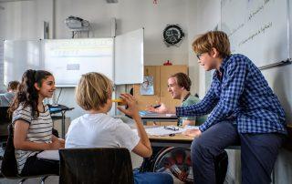Gelebte Inklusion: Schülerinnen und Schüler im Teenageralter unterhalten sich in einem Klassenraum, Copyright: Andi Weiland | Gesellschaftsbilder.de