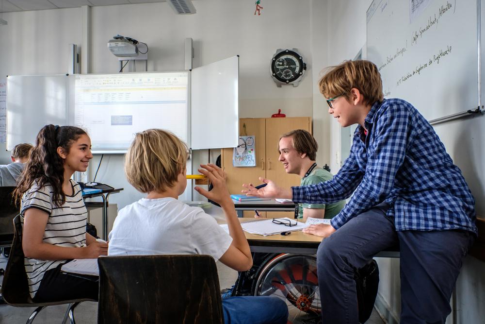 Gelebte Inklusion: Schülerinnen und Schüler im Teenageralter unterhalten sich in einem Klassenraum, Copyright: Andi Weiland   Gesellschaftsbilder.de