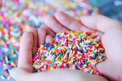 Frau hält bunte Zuckerkonfett in den Händen, Foto: Unsplash