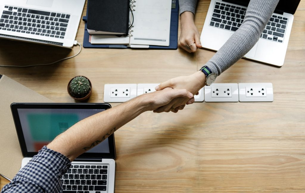 Arbeitnehmer geben sich am Arbeitsplatz die Hand, Credit: Unsplash