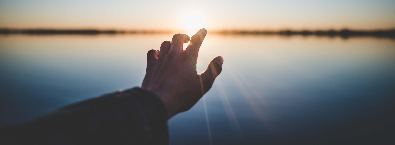 Symboldbild Zuversicht: Männerhand ausgestreckt Richtung Sonne, Credit: Marc-Olivier Jodoin, Unsplash