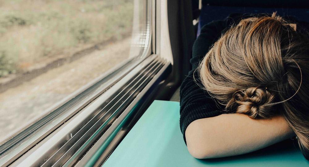 müde Frau schläft im Zug, Credit: Abbie Bernet, Unsplash