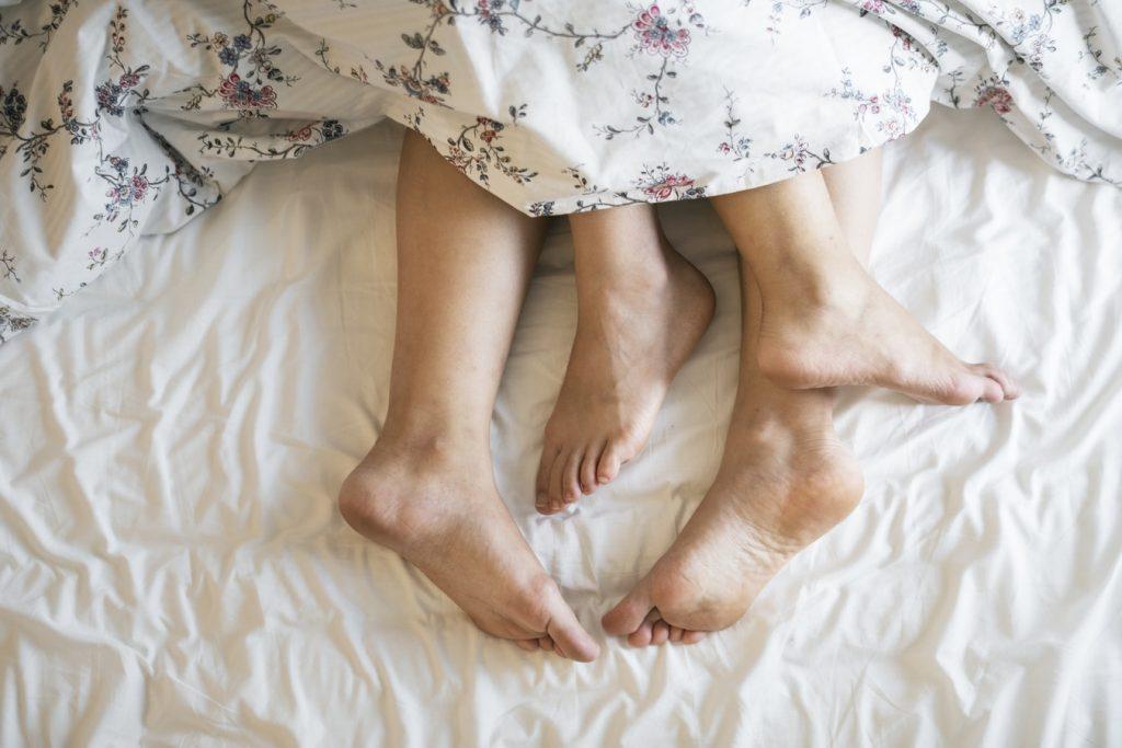 Symbolbild Sexualität: Füße von zwei Personen unter einer Bettdecke, Credit: rawpixel, Unsplash
