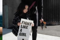 """Mädchen trägt Schild mit Aufdruck """"fight like a girl"""", Credit: Rochelle Brown, Unsplash"""