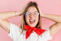 junge Frau mit Brille und rotem Halstuch schreit mit geschlossenen Augen vor rosa Hintergrund, Credit: Ericka Leigh, Unsplash