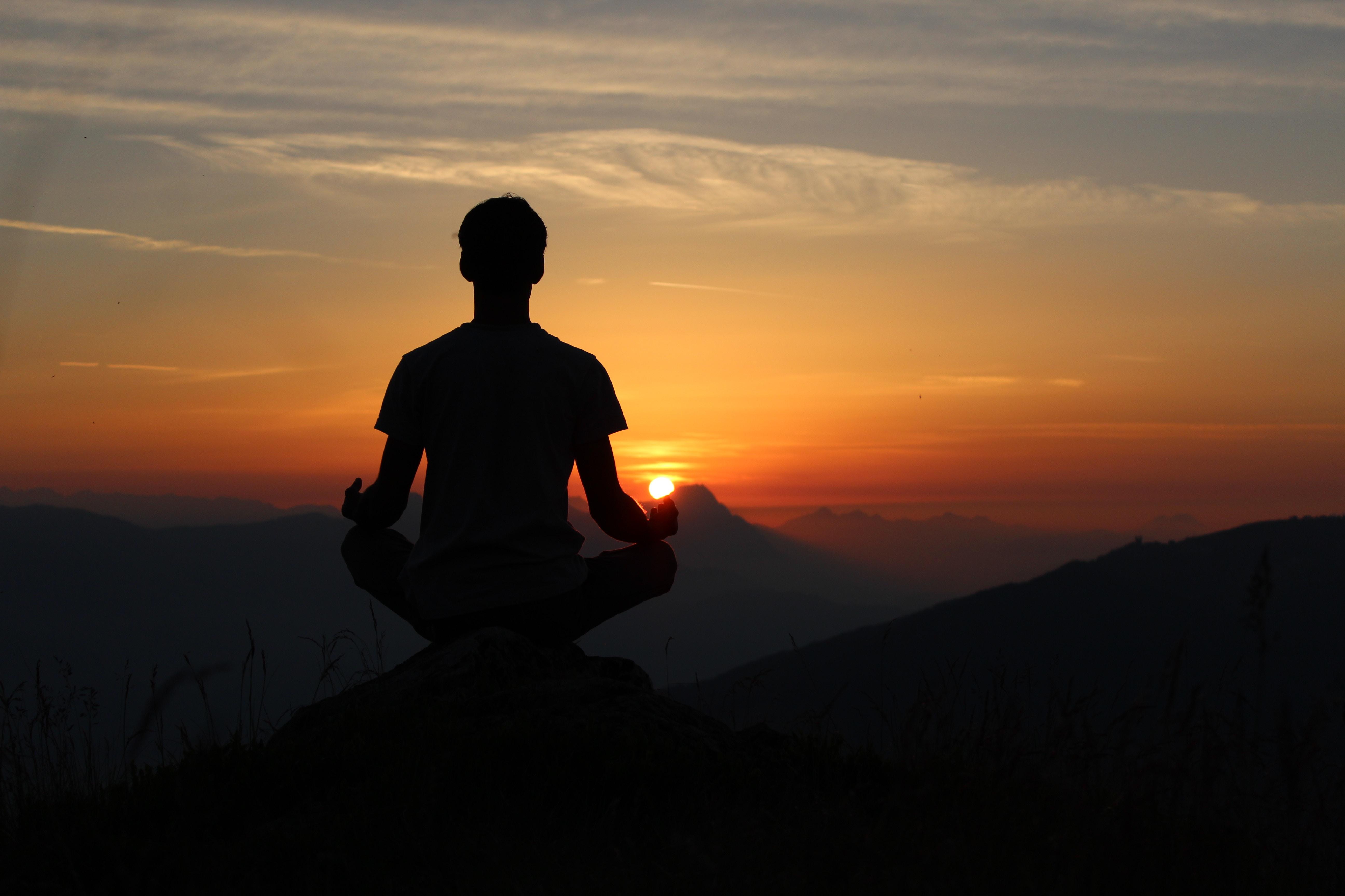 Mann übt Yoga auf einem Berg bei Sonnenuntergang, Credit: Unsplash