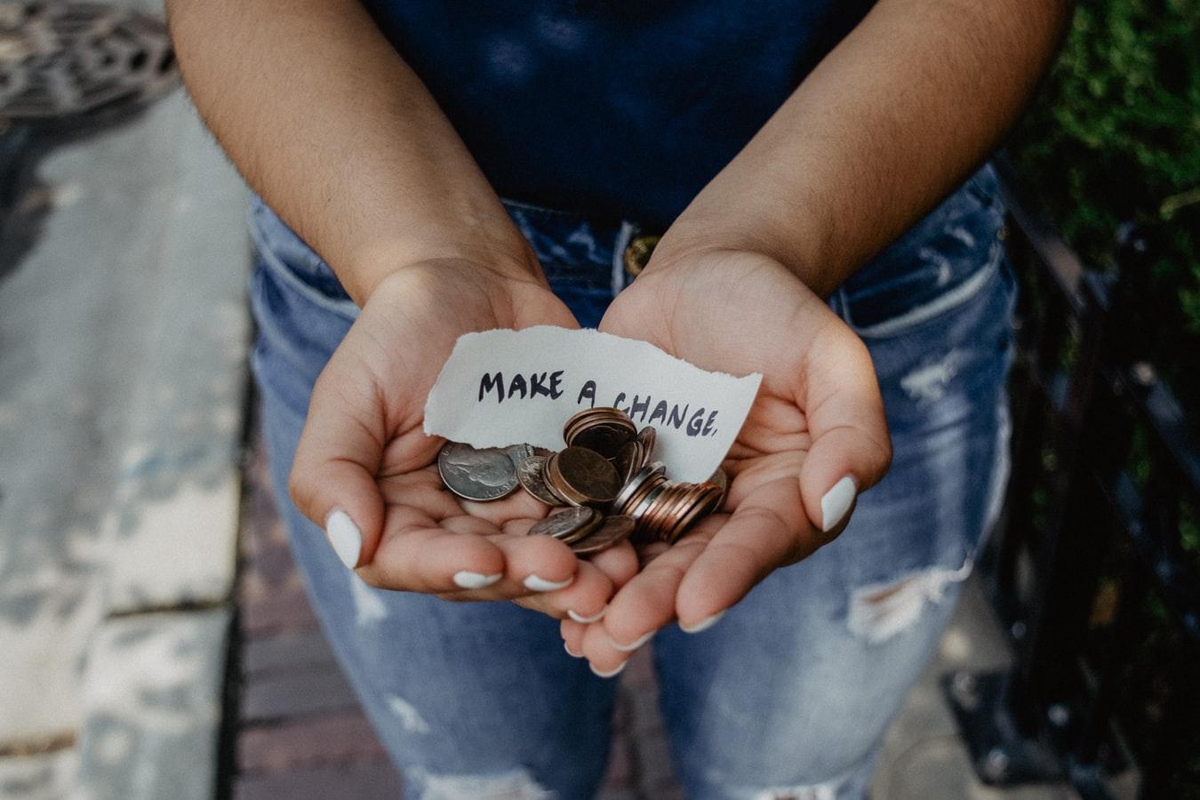 """Frau hält Geld und Zettel mit Aufschrift """"make a change"""" in Händen, Credit: Kat Yukawa, Unsplash"""