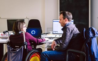 Frau im Rollstuhl und Mann vor einem Schreibtisch, Bildnachweis: Andi Weiland | Gesellschaftsbilder.de