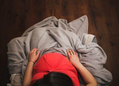 schwangere frau mit schwarzem Haar, zugedeckt mit grauer Decke, von oben fotografiert, Credit: Sergiu Vălenaș, Unsplash