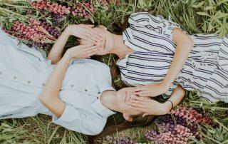 Zwillings-Frauen liegen am Rücken in einer Blumenwiese und halten sich gegenseitig die Augen zu, Credit: Daiga Ellaby, Unsplash