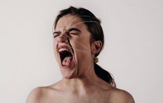 Symbolbild Gewalt: schreiende Frau mit geschlossenen Augen, ihr Kopf ist mit einer Schnur verspannt, Credit: Noah Buscher, Unsplash