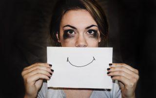 Symbolbild Depression: Junge Frau mit von Wimperntusche verschmeirten Augen sieht hält sich Zettel mit lachendem Gesicht vor den Mund. Credit: Unsplash