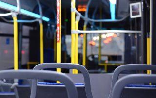 Innenraum einer leeren Straßenbahn, mehrere Sitzlehnen von hinten und der Blick aus der Windschutzscheibe auf den Verkehrsfluss.