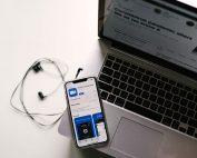 """Tisch mit Computer und Handy, auf dem die App """"Zoom"""" abgebildet ist, Photo by Allie on Unsplash"""