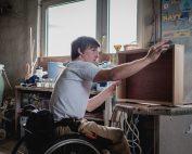 Junger Mann mit Rollstuhl arbeitet in Tischlerei, Bildnachweis: Andi Weiland   Gesellschaftsbilder.de