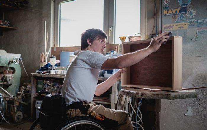 Junger Mann mit Rollstuhl arbeitet in Tischlerei, Bildnachweis: Andi Weiland | Gesellschaftsbilder.de