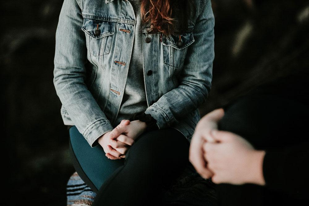 Symbolbild Psychotherapie: Junge Frau mit Jeansjacke und gefalteten Hände, Credit: Priscilla Du Preez on Unsplash