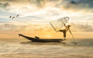 Ein Fischer balanciert einbeinig auf einem Fischerboot am Meer