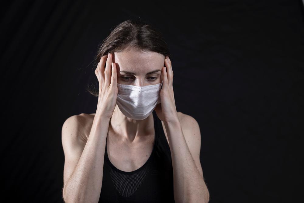 Frau mit Maske und an die Schläfen gehaltenen Händen. Foto: Engin Aykurt, Unsplash