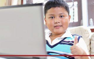 Schüler sitzt vor Laptop und hält Daumen nach obne, Credit: Canva