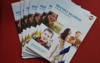 """7 Ausgaben der Broschüre"""" Multiple Sklerose: 25 Fragen und Antworten"""" liegen auf einem roten Stoff. Herausgegeben von der Multiple Sklerose Gesellschaft Wien im November 2020"""