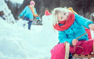 Mädchen auf Schlitten im Schnee, Foto: Gerhard Berger, SOS Kinderdorf