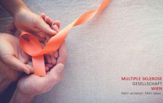 Mache kleine Dinge mit großer Liebe: Mutter hält Hand ihres Kindes, orange Schleife, Credit: Canva