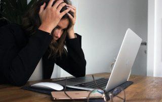Symbolbild Fatigute: Frau stützt Kopf auf die Hände, während sie vor einem Laptop sitzt, Photo by Elisa Ventur on Unsplash