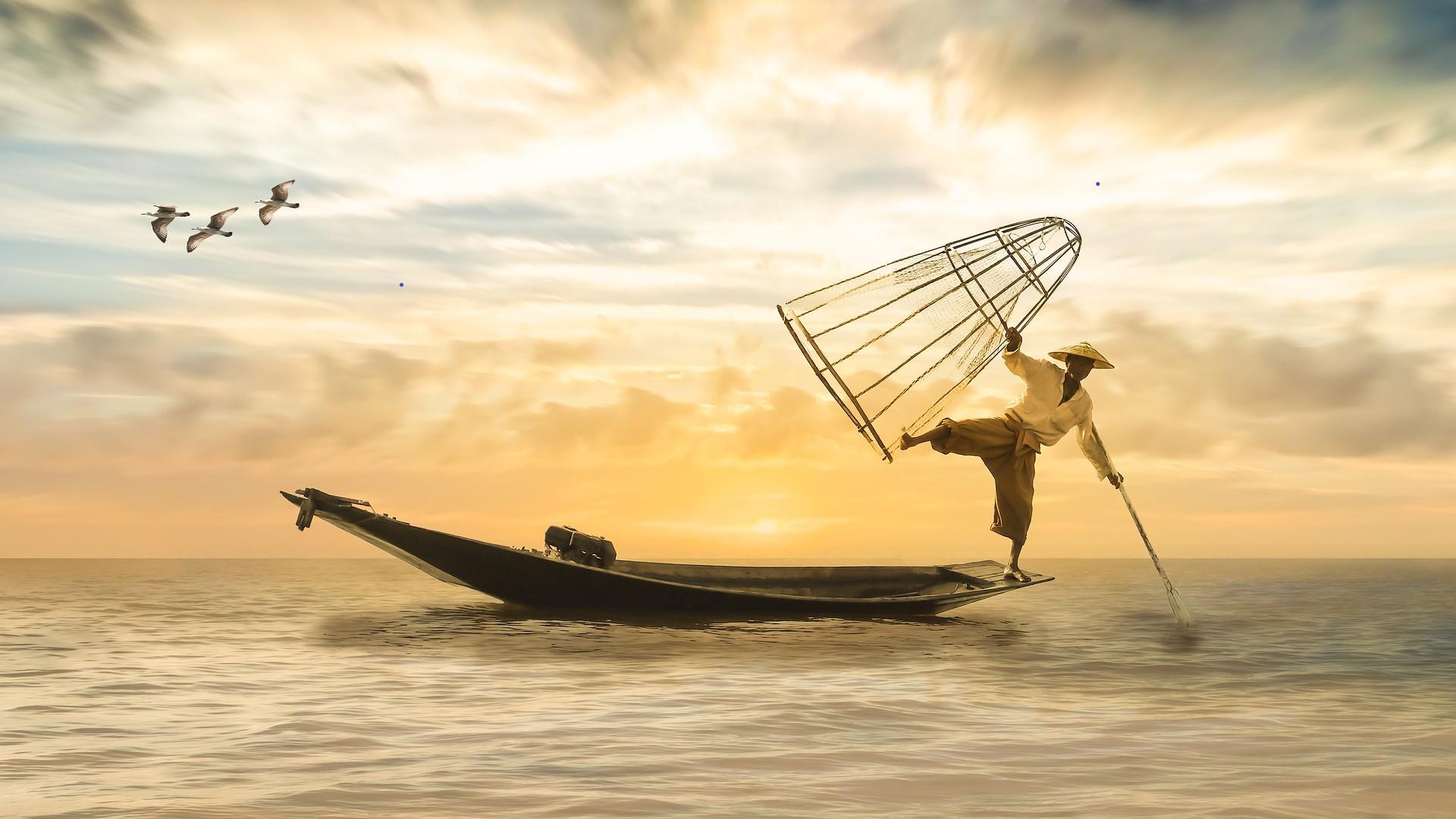 Balancierender Fischer auf Fischerboot im Sonnenuntergang